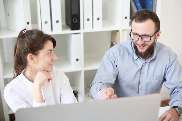 Trabalho em equipe homem e mulher no escritório. olhe para o monitor do computador