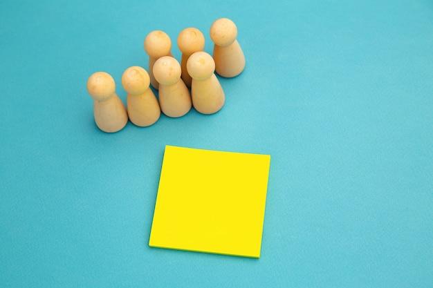 Trabalho em equipe, maquete de teambuilding, estrutura da empresa. figuras de madeira perto de um post-it amarelo, lugar para texto