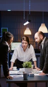 Trabalho em equipe multiétnico diversificado em torno de uma mesa, debatendo ideias de empresas