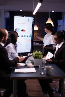 Trabalho em equipe multiétnico diversificado em trabalho excessivo na sala de reuniões do escritório, analisando gráficos financeiros
