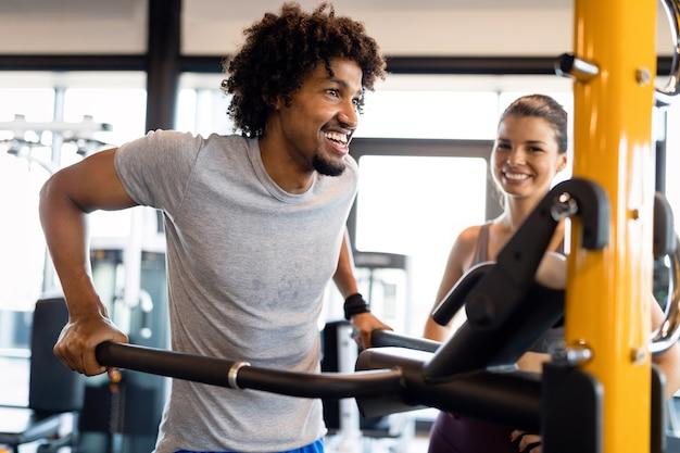 Trabalho em equipe na academia. casal trabalhando exercício juntos. conceito de vida saudável