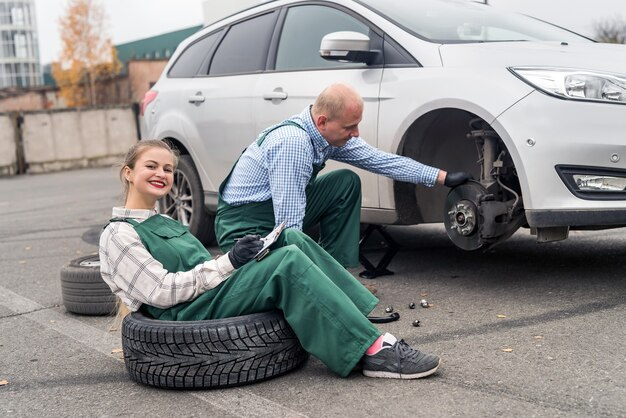 Trabalho em equipe na estação de serviço do carro, verificação do disco de freio