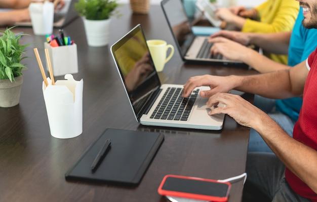 Trabalho em equipe na moda jovem, usando o computador no escritório criativo de coworking - pessoas de negócios, trabalhando juntos no novo projeto de aplicativo - foco na mão do close-up - conceito de tecnologia, marketing e emprego