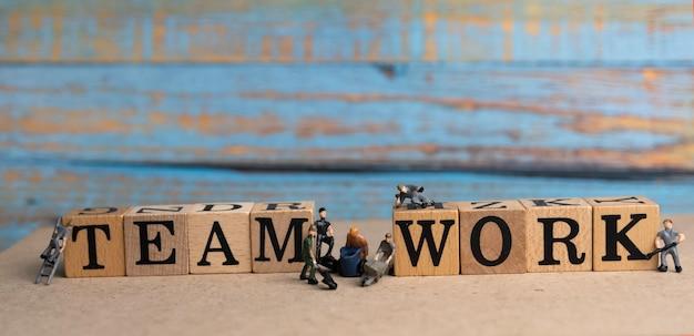 Trabalho em equipe palavra escrita em bloco de madeira e bonecos colocados em tábuas de madeira, luz desfocada ao redor