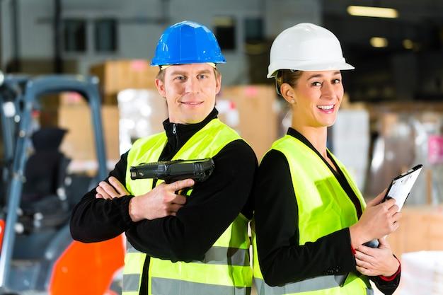 Trabalho em equipe trabalhador ou armazém com scanner e seu colega de trabalho com a área de transferência no armazém da empresa de expedição de mercadorias