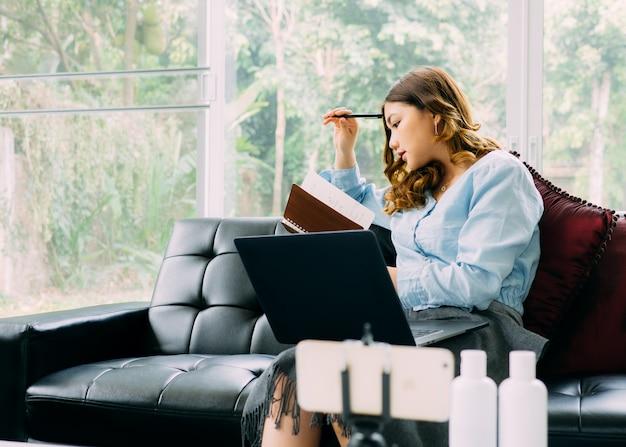 Trabalho em linha do internet da mulher consideravelmente asiática em casa e relaxe o estilo de vida com seu labtop
