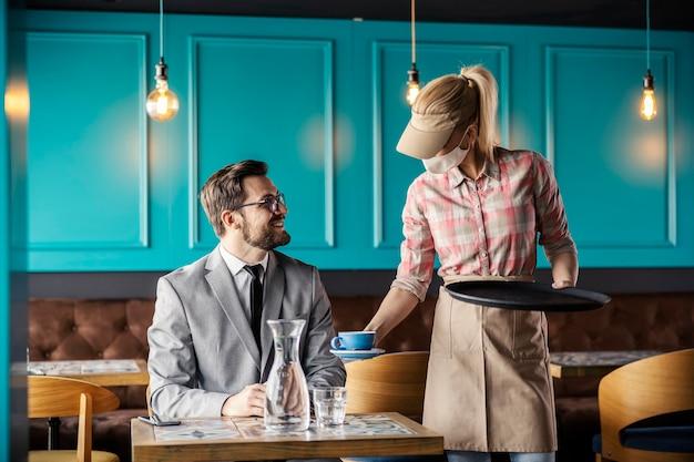 Trabalho em restaurante e vírus corona. garçonete está usando uniforme e máscara protetora. ela deixa uma garrafa de água e uma xícara de café na mesa e atende o convidado de terno em um restaurante