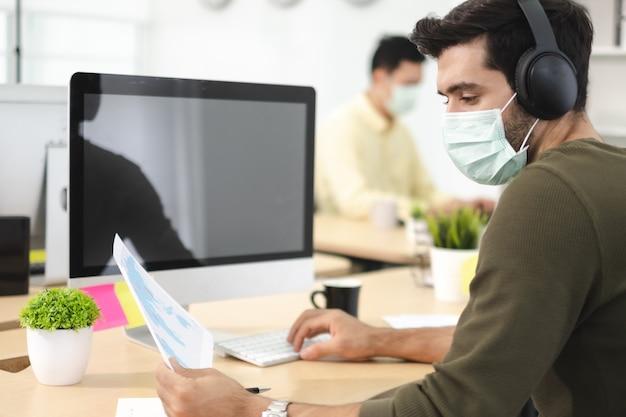 Trabalho empresarial no escritório com máscara facial, quarentena de distanciamento social durante covid19 afeta