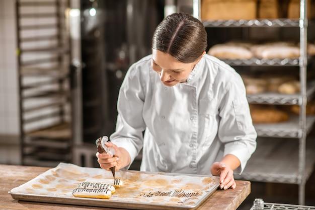 Trabalho favorito. chef de confeitaria atenciosa interessada em uma jaqueta branca, decorando éclairs com padrão de chocolate na padaria