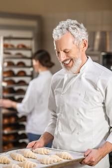Trabalho favorito. homem de barba cinza feliz olhando para a bandeja de croissants nas mãos e uma mulher ocupada atrás de uma padaria