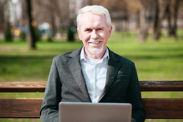 Trabalho favorito. homem de negócios maduro satisfeito usando laptop enquanto sorri para a câmera
