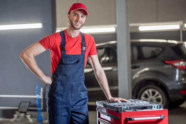 Trabalho favorito. jovem adulto alegre mecânico de automóveis de boné e macacão em pé perto da caixa de ferramentas na oficina
