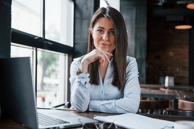 Trabalho freelance. mulher de negócios com roupas oficiais está dentro de casa no café durante o dia.