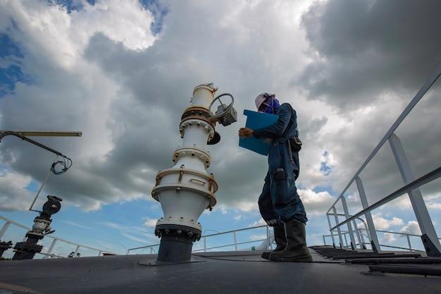 Trabalho masculino inspeção visual bico de telhado tanque de armazenamento óleo nuvens de fundo céu azul