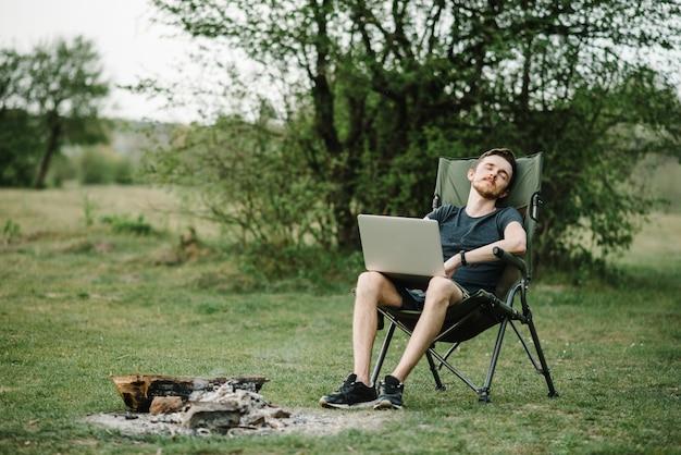 Trabalho masculino remoto no laptop enquanto aprecia a natureza