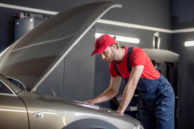 Trabalho, mecânico de automóveis. jovem sério barbudo de macacão olhando para o capô do carro pensando com atenção