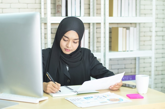 Trabalho muçulmano da jovem mulher no escritório usando o telefone