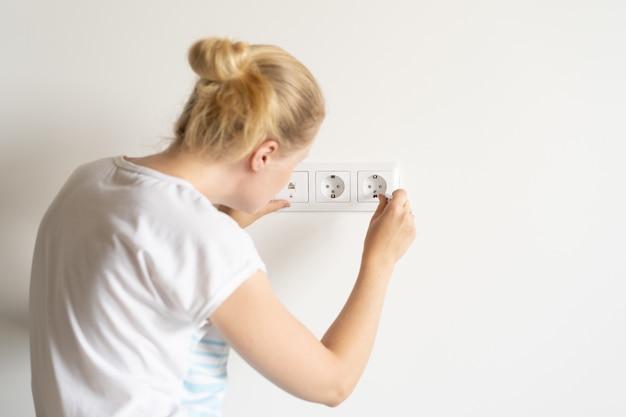 Trabalho não feminino. reparação e decoração. mulher repara tomadas em um apartamento novo