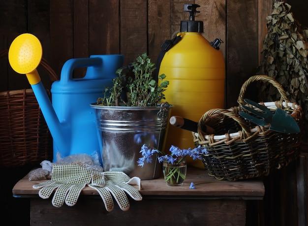 Trabalho no jardim. ferramentas de jardim: regador, pá, balde, luvas na mesa.