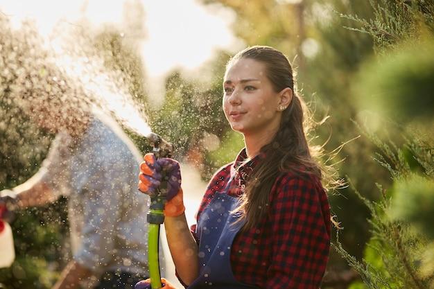 Trabalho no jardim. o jardineiro da menina pulveriza água e um cara pulveriza fertilizante nas plantas no belo viveiro-jardim em um dia ensolarado. .