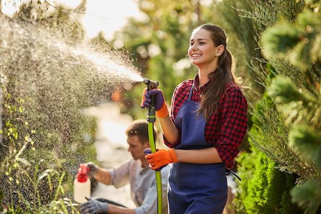 Trabalho no jardim. o jardineiro da menina sorridente pulveriza água e um cara pulveriza fertilizante nas plantas no belo viveiro-jardim em um dia ensolarado. .