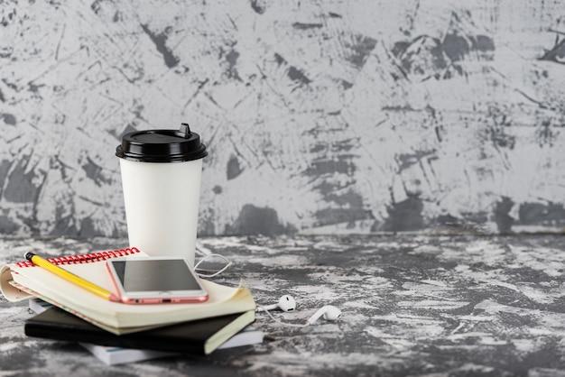Trabalho ou educação em movimento. xícara de café, fruta da manga, smartphone rosa e pilha de blocos de notas na mesa de pedra cinza. copie o espaço.