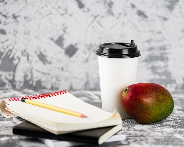 Trabalho ou educação em movimento. xícara de café, fruta da manga, telefone e pilha de blocos de notas na mesa de pedra cinza. copie o espaço.