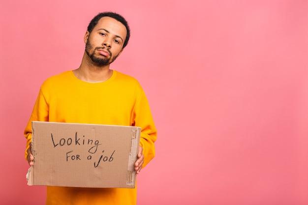 Trabalho, por favor. jovem desempregado segurando um papelão escrito à mão implorando por um emprego durante uma crise de infecção por coronavírus isolada em rosa