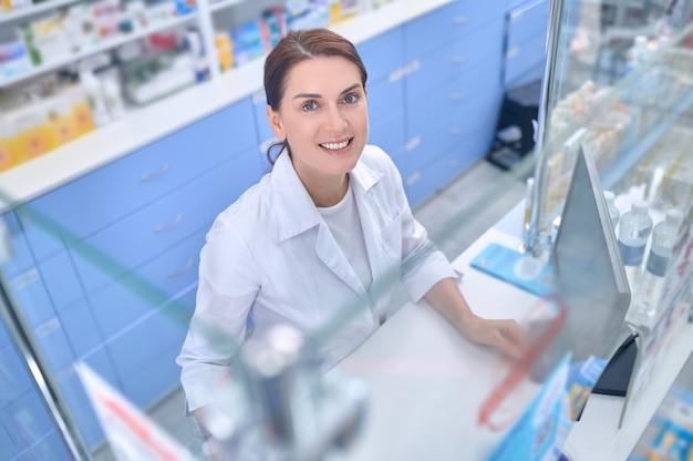 Trabalho, positivo. mulher adulta jovem sorridente de jaleco branco em pé perto da caixa registradora da farmácia olhando para cima