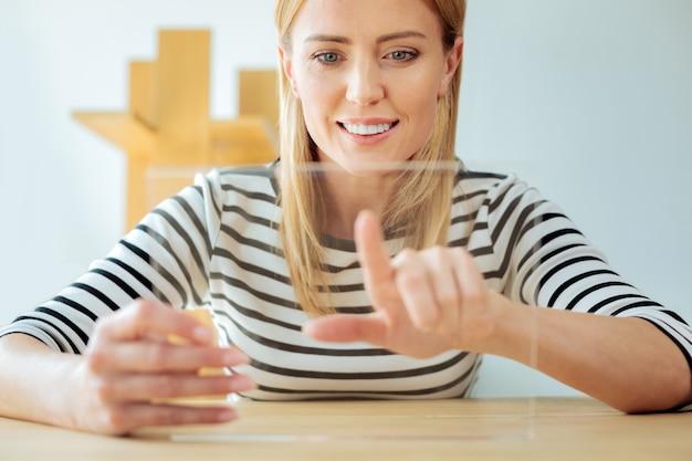 Trabalho prazeroso. mulher jovem, feliz e positiva, sorrindo e de ótimo humor enquanto trabalha com tecnologia inovadora