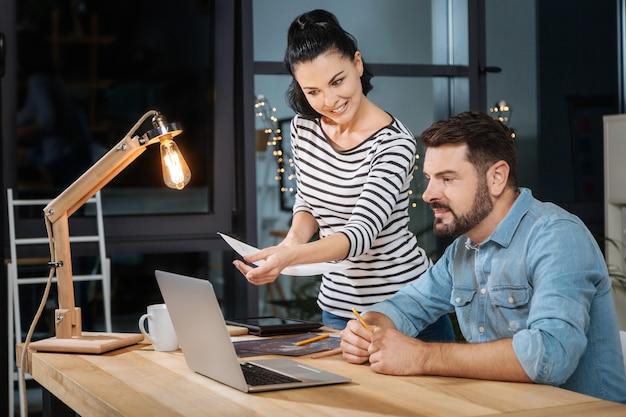 Trabalho produtivo. colegas alegres, que trabalham duro, olhando para a tela do laptop e sorrindo enquanto desfrutam de seu trabalho cooperativo
