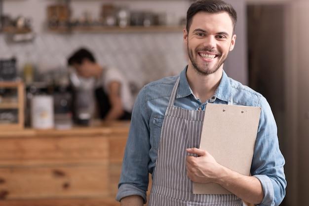 Trabalho relaxado. jovem atraente segurando uma pasta e sorrindo em pé em um café.