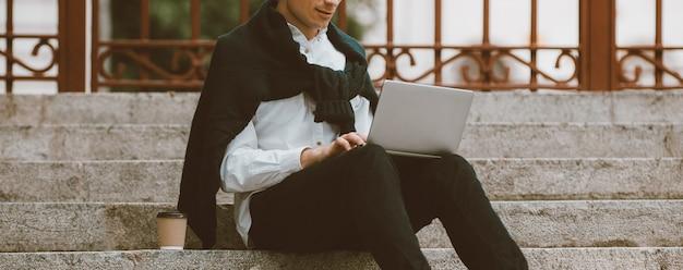 Trabalho remoto. comunicação online. freelancer masculino relaxado sentado na escada trabalhando no laptop.