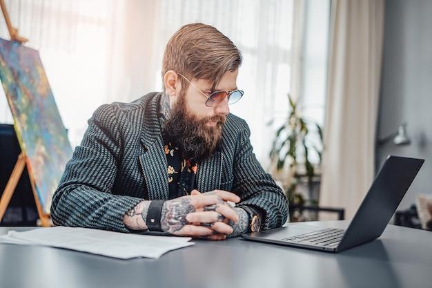 Trabalho remoto e estilo de vida doméstico. hipster caucasiano com barba e tatuagens se senta à mesa no escritório em casa moderno.