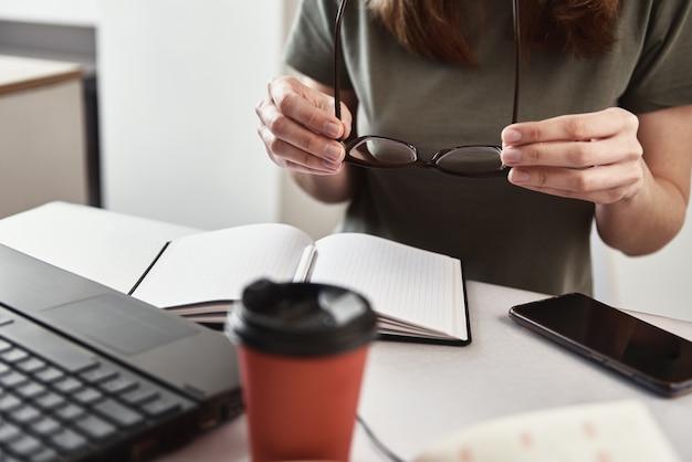 Trabalho remoto freelancer de conceito de trabalho em casa mulher segura óculos nas mãos no local de trabalho
