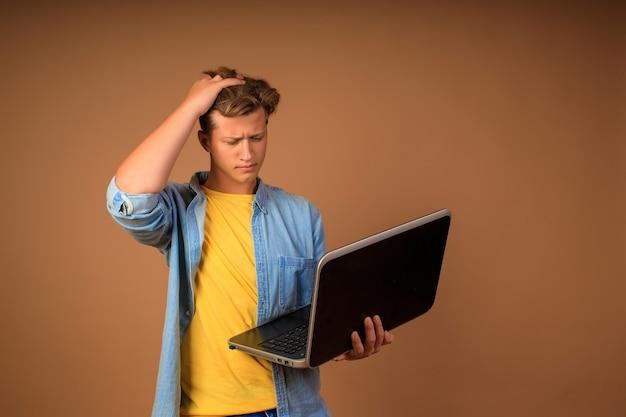 Trabalho remoto moderno. retrato de um jovem com um laptop nas mãos em uma parede bege