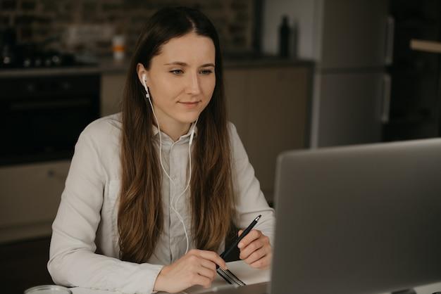 Trabalho remoto. uma mulher morena caucasiana com fones de ouvido trabalhando remotamente on-line em seu laptop. uma garota em uma camisa branca, fazendo uma vídeo chamada para seus parceiros de negócios em seu local de trabalho em casa.
