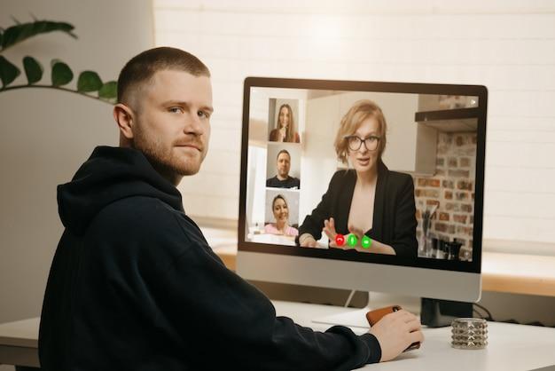 Trabalho remoto. vista traseira de um homem durante uma vídeo chamada com seus colegas no computador desktop. um colega distraído de um briefing on-line em casa.