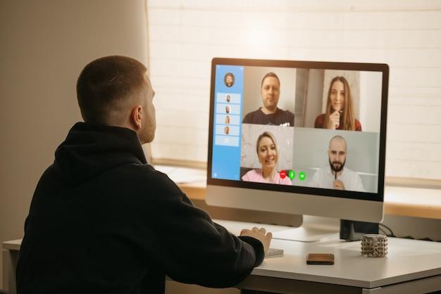 Trabalho remoto. vista traseira de um homem durante uma vídeo chamada com seus colegas no computador desktop. um colega em um briefing on-line trabalhando em casa.