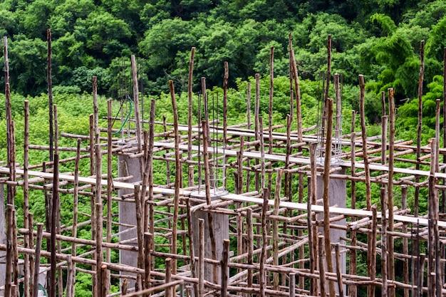Trabalhos de construção com cimento e madeira, colunas de argamassa de betonagem, andaimes e trabalhos de construção, edifícios na floresta