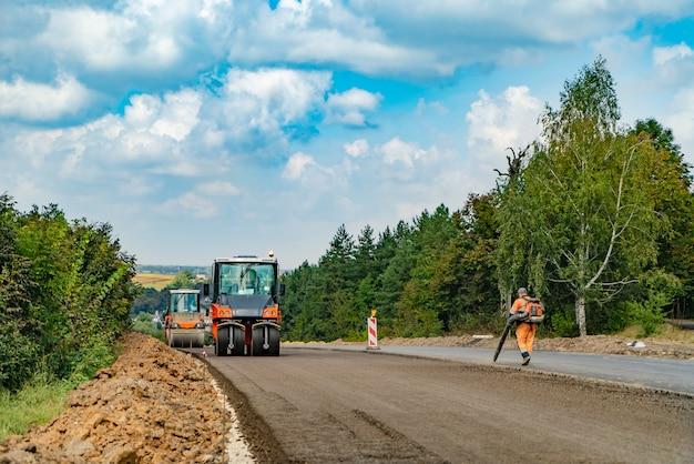 Trabalhos de construção de estradas com compactador de rolos e finalizador de asfalto
