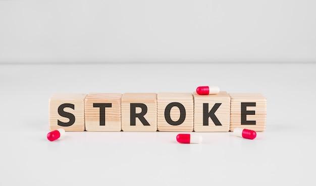 Traço de palavra feito com blocos de madeira com pílulas vermelhas, conceito médico.