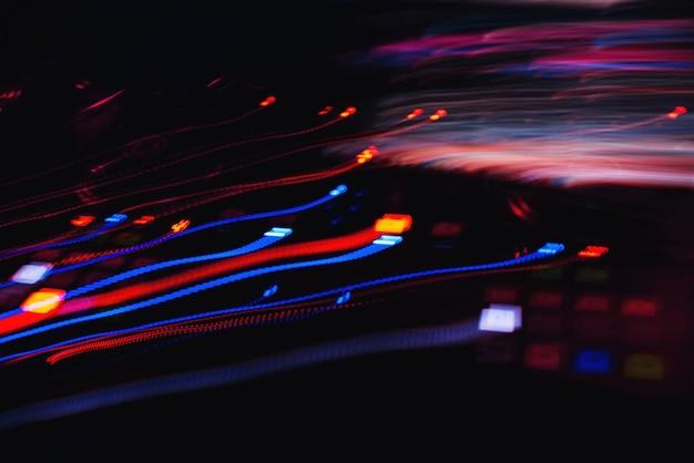 Traços coloridos abstratos de efeitos na longa exposição de equipamentos musicais de botões de luz