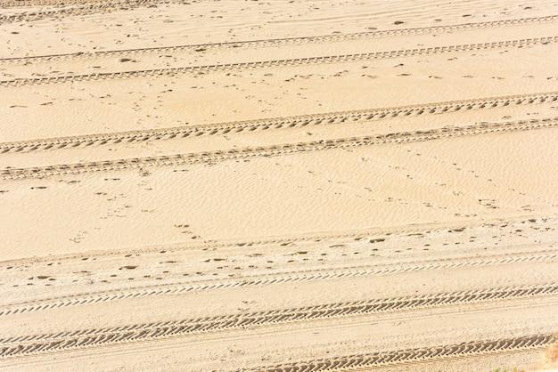 Traços de pneus de carro na areia como pano de fundo