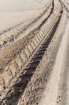 Traços de pneus de carros industriais em fundo de areia