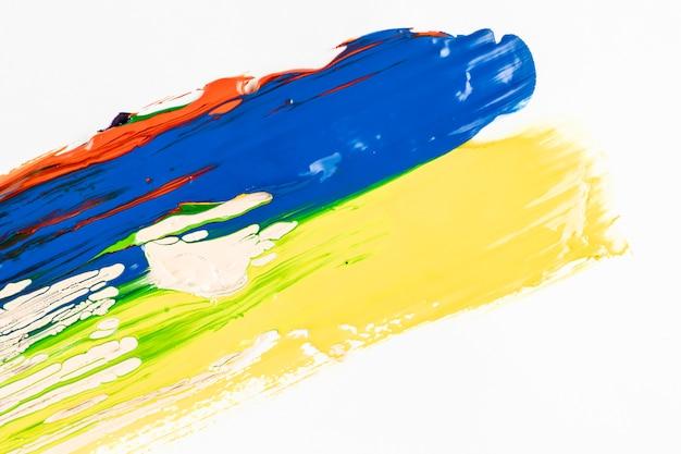 Traços de tinta azul e amarelo sobre fundo branco