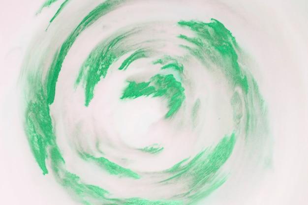 Traços de tinta verde artística em forma circular no fundo branco