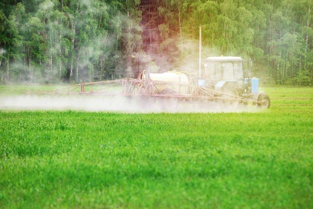Tractror pulverizando pesticidas, inseticidas ou herbicidas