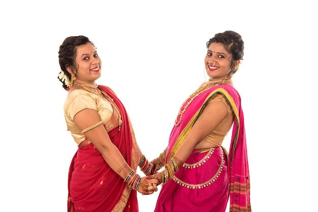 Tradicionais lindas garotas indianas em sari posando em branco
