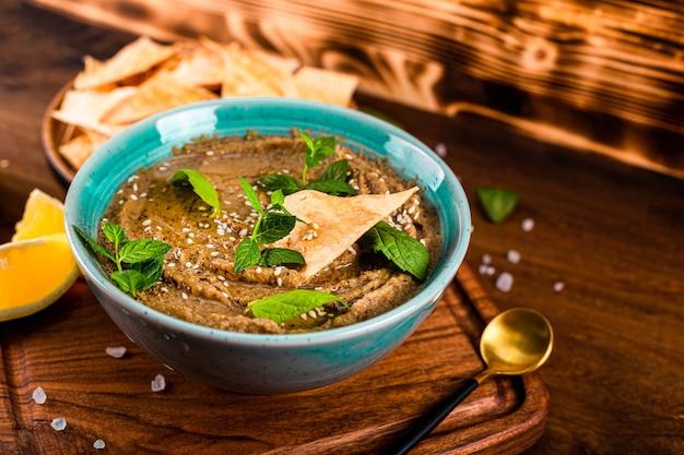 Tradicional aperitivo oriental baba ganoush com gergelim e close-up de folhas de hortelã. hummus de berinjela com batatas fritas de pita na mesa de madeira.